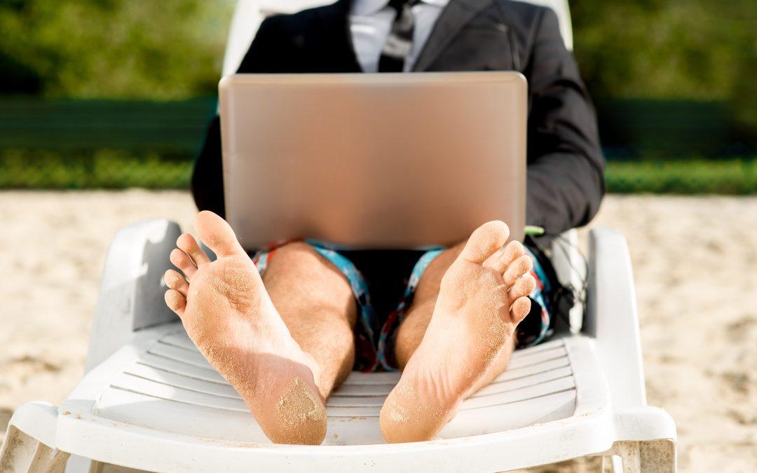 Man op strand met laptop